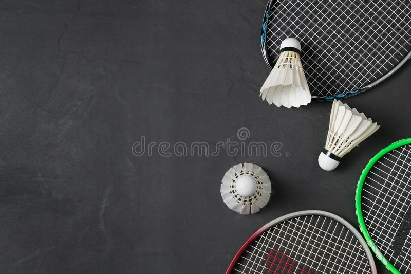 Shuttlecocks and badminton racket on black background. stock photography