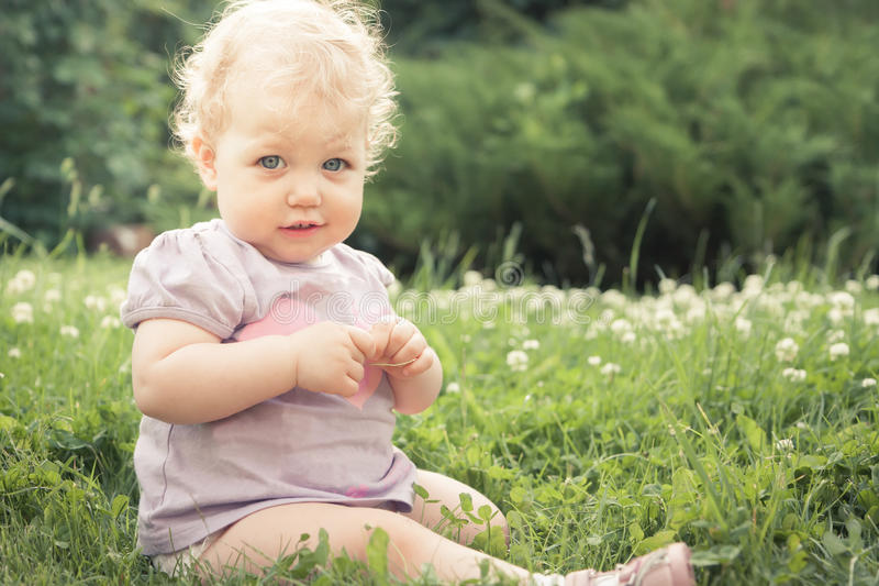 Shy baby girl on grass among blossoming flowers in summer park in sunny day with copy space. Shy baby girl in the garden on grass among blossoming flowers in stock photos