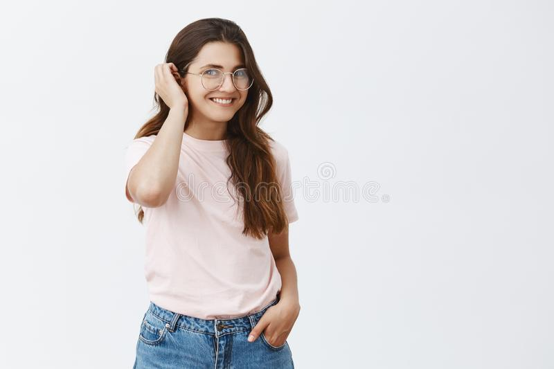 Shy friendly and cute brunette female in pink t-shirt and jeans putting hair strand behind ear and smiling broadly stock photo