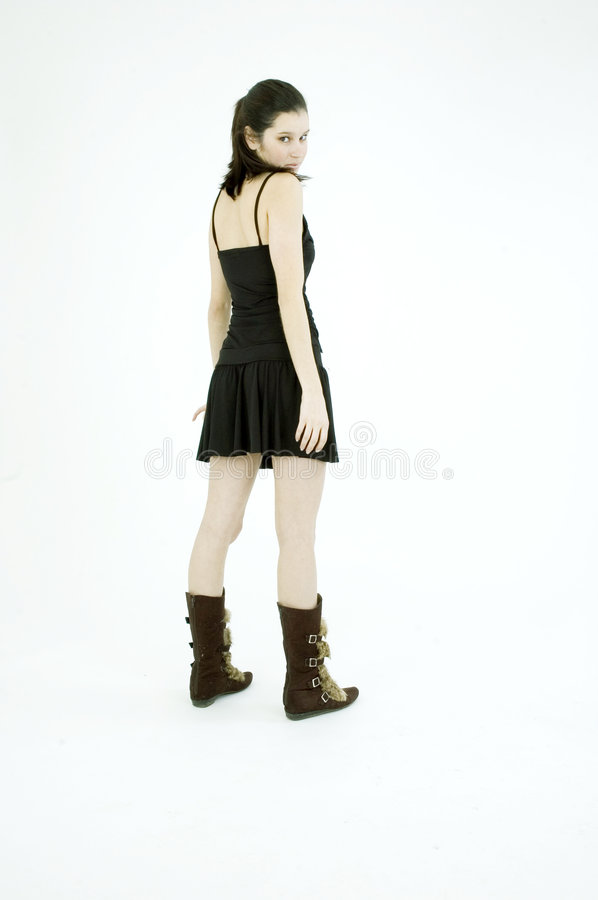 Shy girl. Young brunette, in black short skirt and trendy fur boots, poses shy on a white background stock photos
