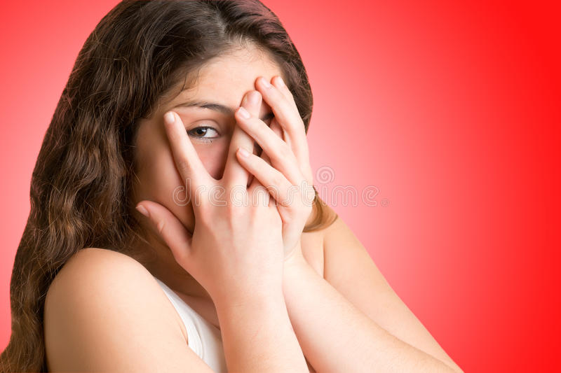 Shy Girl. Covering up her face with her hands, isolated royalty free stock photo