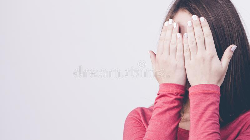 Shy girl hides her face stock images