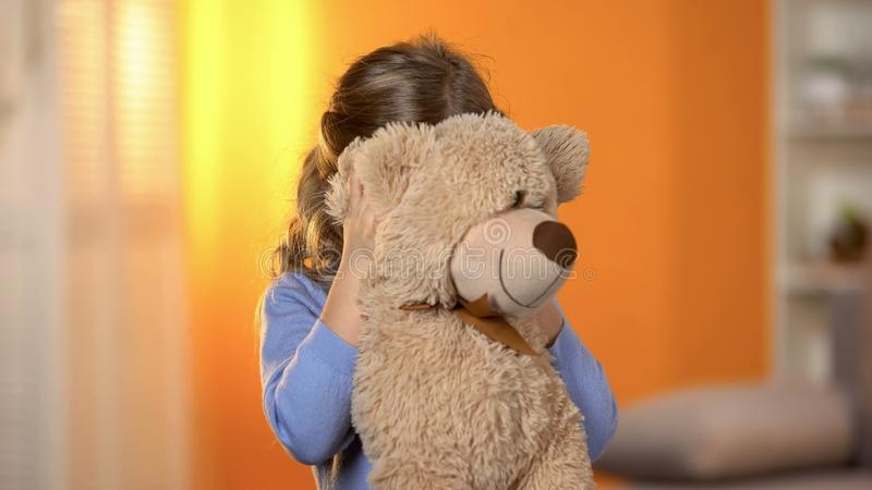 Shy girl hiding behind plush toy, preschooler feeling lonely and hopeless royalty free stock photo