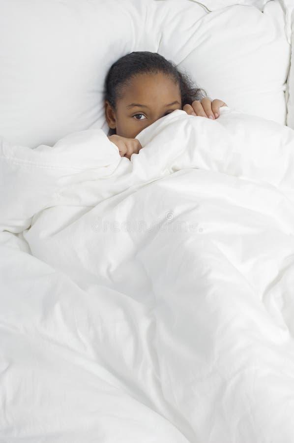 Shy Girl Hiding Under Duvet stock images