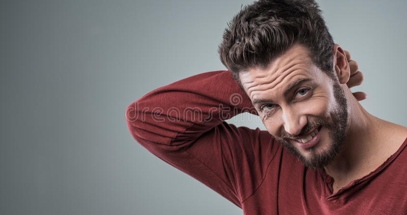 Shy guy with hand behind head. Shy attractive guy smiling at camera with hand behind head royalty free stock image