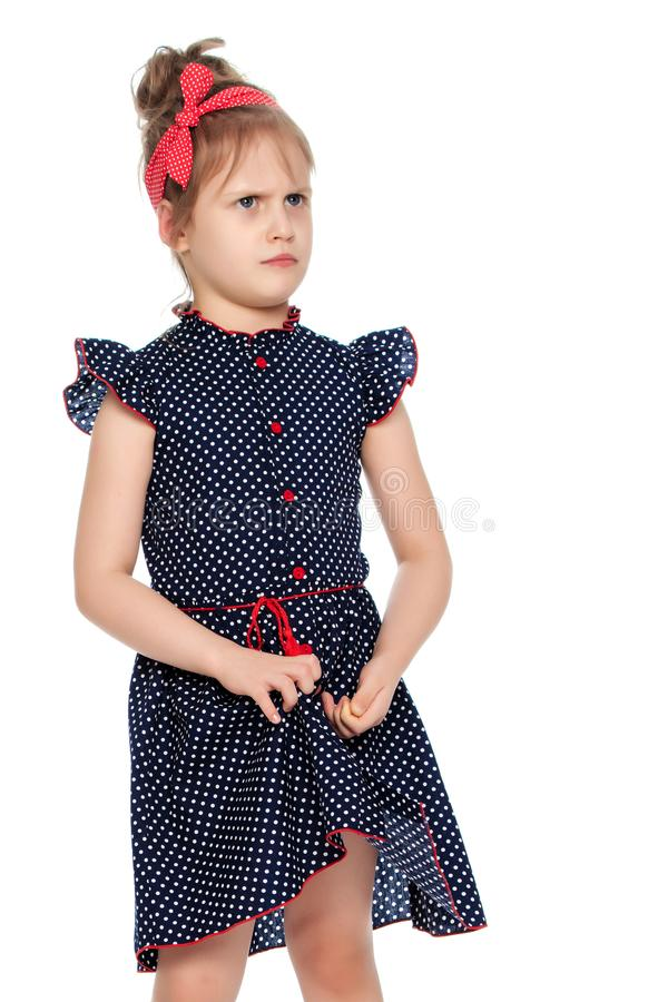 Shy little girl in the blue dress. stock photography