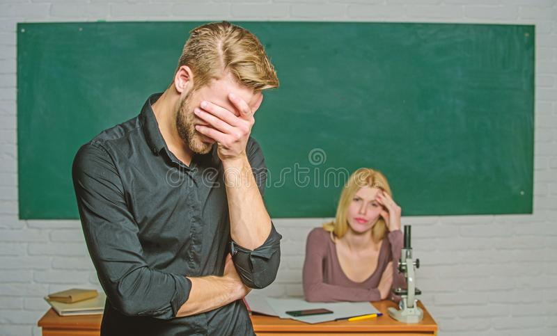 He is so shy. Male student with examiner at examination. High school student saying lesson. Handsome man standing in. He is so shy. Male student with examiner at stock photos
