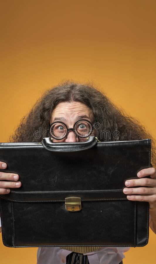 Shy nerd hiding behind the brief case stock photo