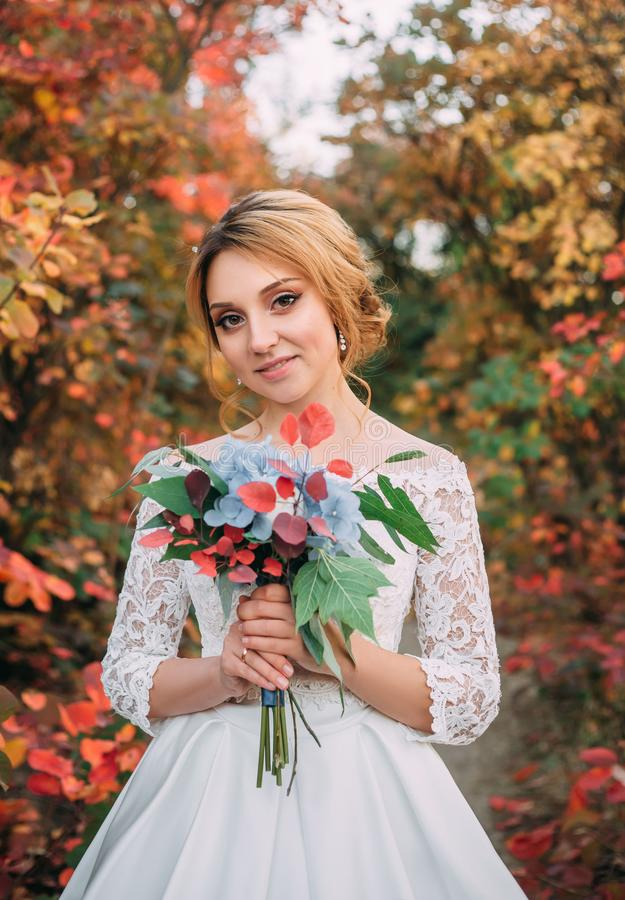 Shy nice cute young bride in elegant white long dress with blue and red bouquet of flowers in hands standing in red stock photography