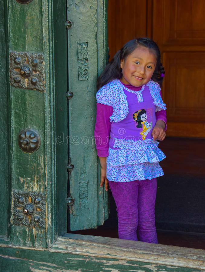 Shy Peruvian Girl. A young Peruvian girl clings to the doorway of a church as she is caught playing hide and seek with her siblings. Upon noticing me she stops royalty free stock photo