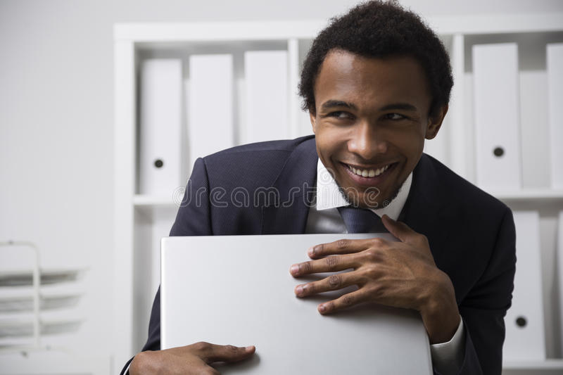Shy and smiling African American clerk. Portrait of a very shy African American office clerk working in a white office, smiling and grasping his laptop as a stock images
