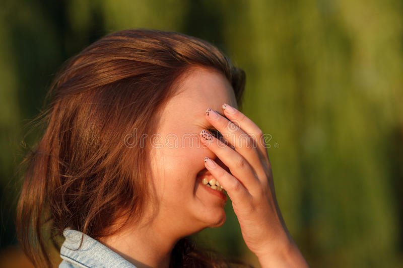 Shy teenage girl. Close-up portrait of shy teenage girl hiding her face with hand stock photo