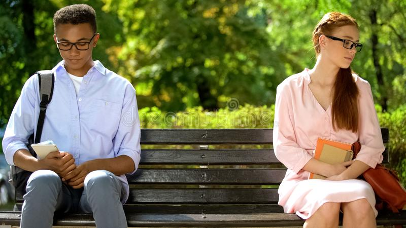 Shy teens sitting on different parts of bench, hesitating to tell about feelings royalty free stock photo