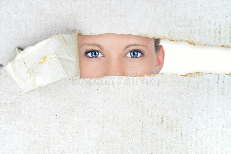 Shy woman, hidden beauty. Shy woman revealing eyes behind paper royalty free stock image