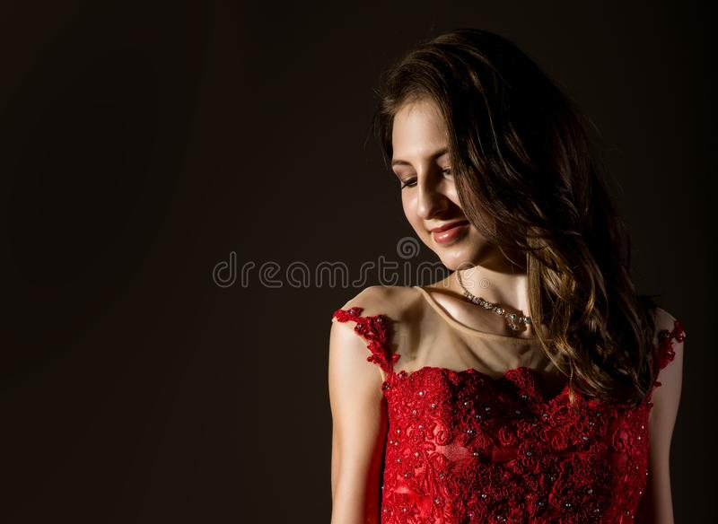 Shy woman lowered her eyes smiles timid. Girl in elegant red dress on a dark background. free space for your text stock images