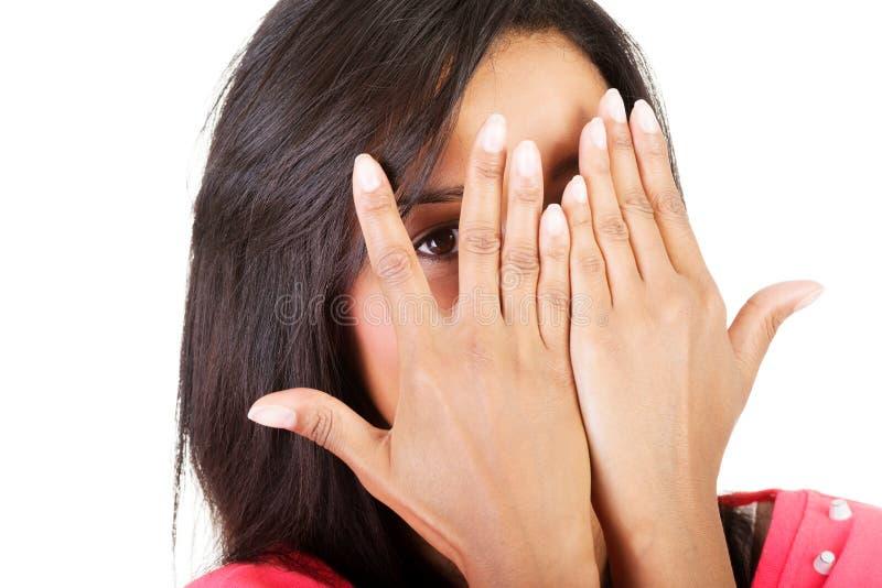 Shy woman peeking through covered face. Shy woman peeking through covered face , isolated on white royalty free stock image