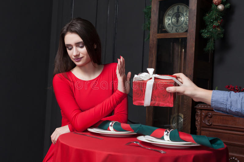 Shy woman refuses gift in restaurant. Couple relationship stock photo