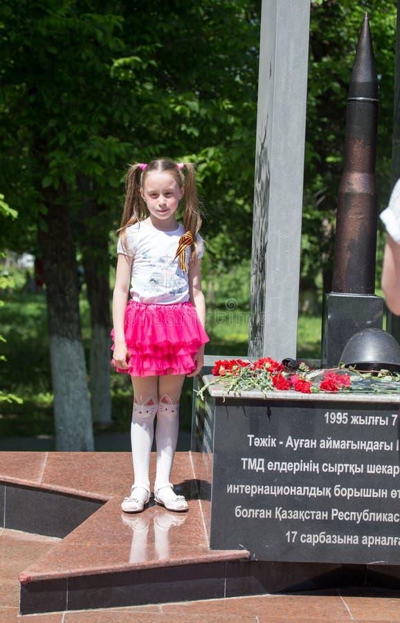 SHYMKENT, KAZAJISTÁN - 9 DE MAYO DE 2017: Una muchacha en Victory Day de la gente del ejército rojo y del soviet en el gran patri fotografía de archivo