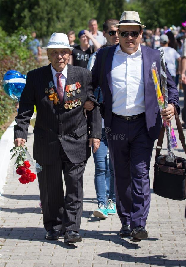 Shymkent, KAZAJISTÁN - 9 de mayo de 2017: Veteranos de la guerra El banquete de la victoria de la gente del ejército rojo y del s fotografía de archivo