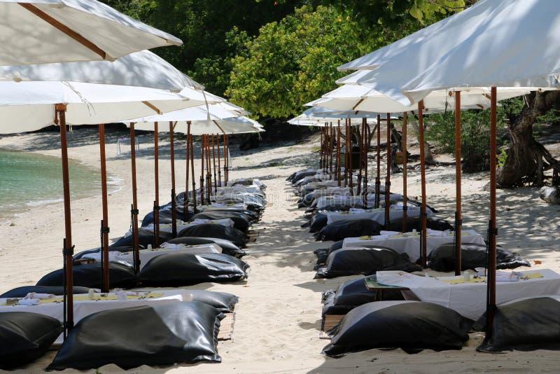 Siège blanc de coussin de parapluie et d'air sur la plage photos stock