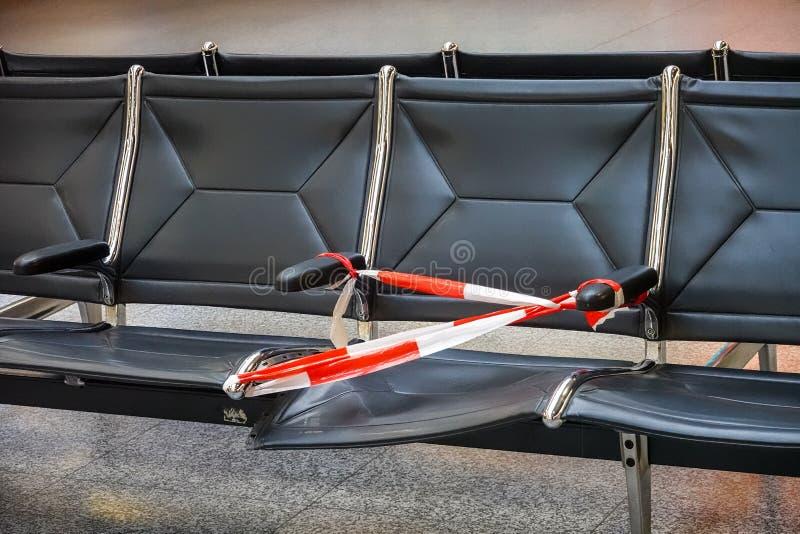 Siège cassé défectueux fixé avec une bande en plastique rouge et blanche de barrière dans le refuge d'un aéroport photo stock