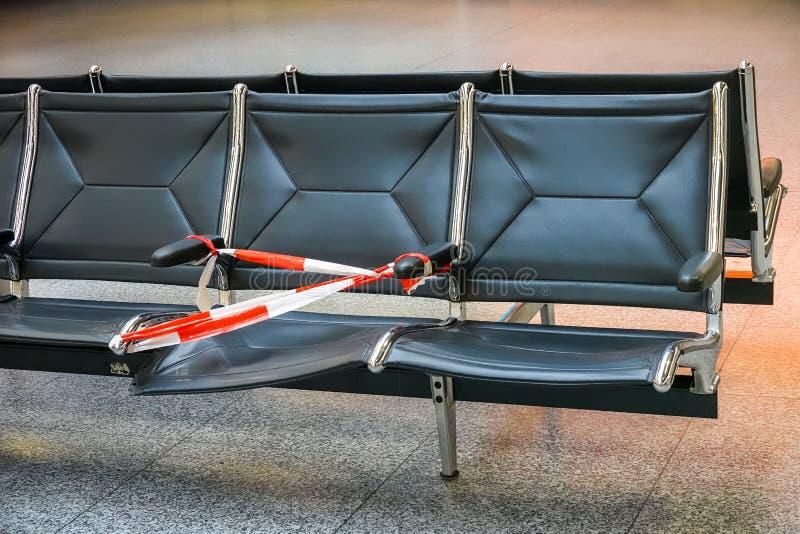 Siège cassé défectueux fixé avec une bande en plastique rouge et blanche de barrière dans le refuge d'un aéroport photographie stock