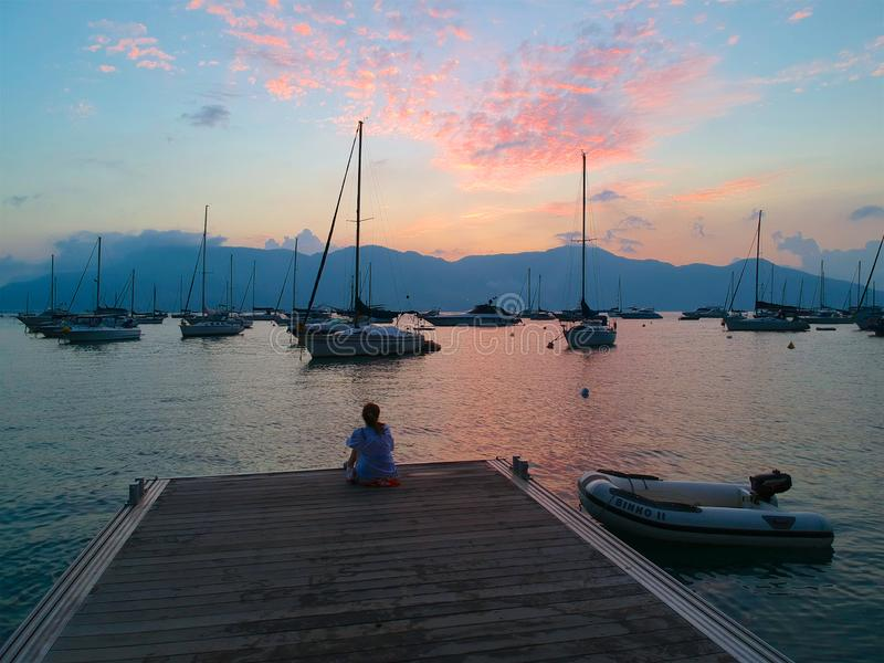 Siège de femme sur un dock regardant le beau coucher du soleil de mer avec le voilier sur la mer et la montagne sur le fond image stock