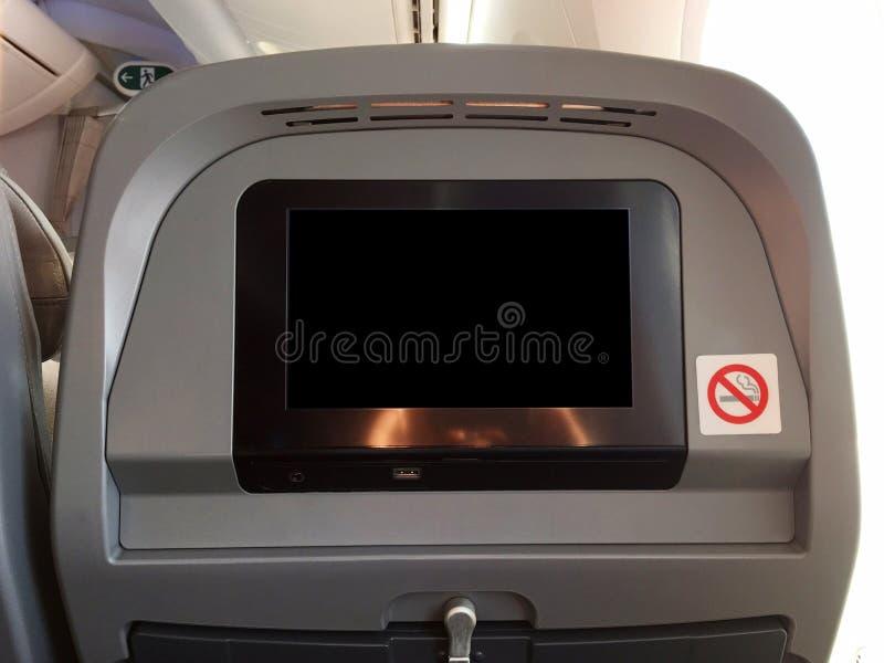 Siège de passager d'avion avec l'écran de moniteur noir vide vide, et signe permis non-fumeurs photo libre de droits