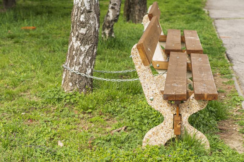 Siège en bois dans la rue avec une chaîne de fer Une chaîne de fer attache un banc en bois sur une rue passante images libres de droits