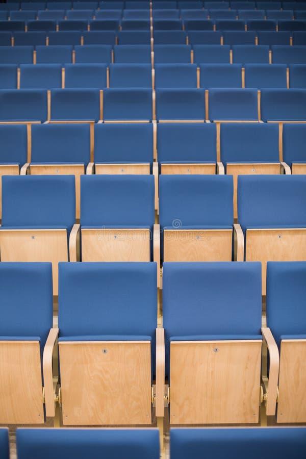 Sièges bleus vides dans une salle de conférence photographie stock