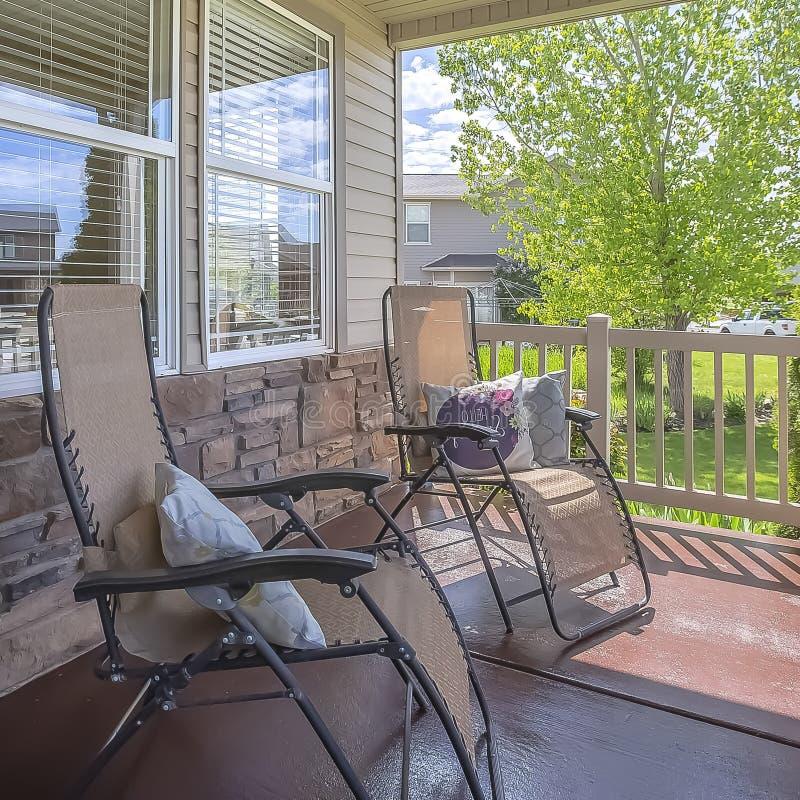 Sièges de détente de cadre carré sur le porche d'une maison avec la vue de l'extérieur ensoleillé image stock