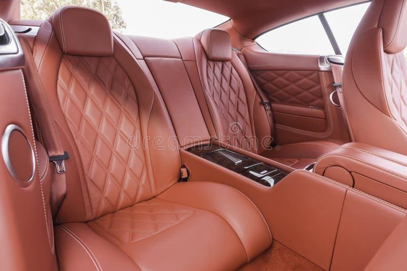 Sièges de passager arrières de rouge dans la voiture confortable de luxe moderne photos stock