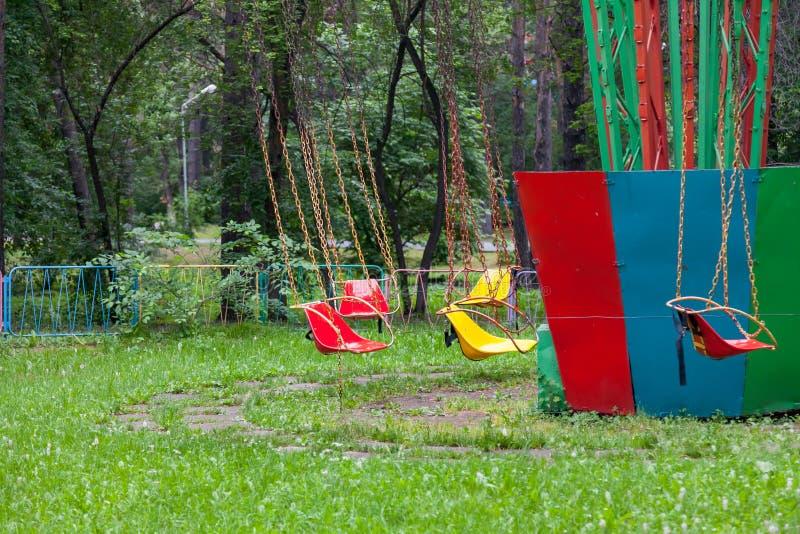 Sièges en plastique jaunes et rouges multicolores accrochant sur le carrousel de chaînes en parc pour le divertissement et l'amus photo libre de droits