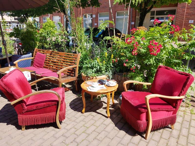 Sièges tapissés rouges confortables dans un café de steeet à Cologne images stock