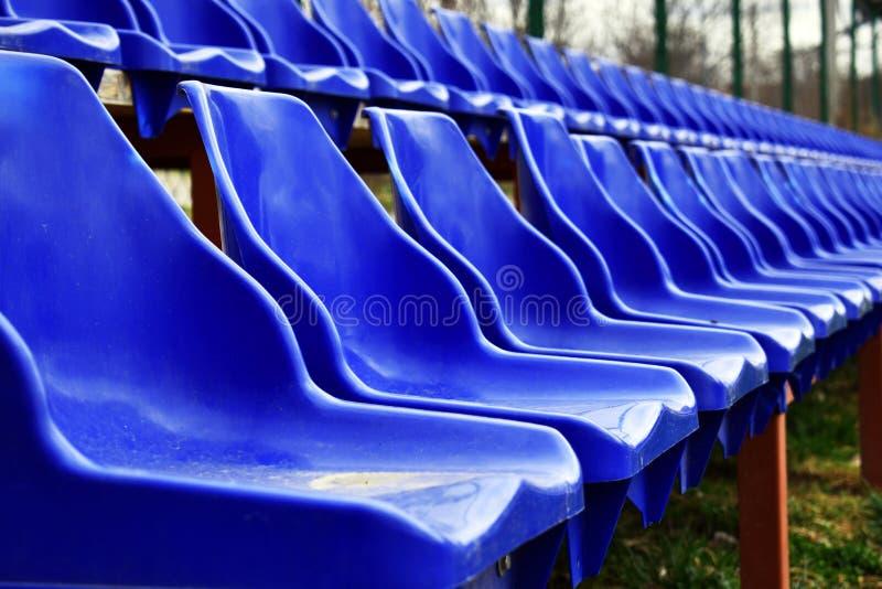 Sièges vides de bleus sur l'au sol de sports en plein air image libre de droits