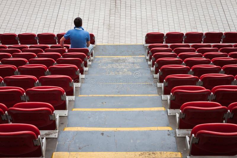 Sièges vides de stade avec un homme seul photo libre de droits