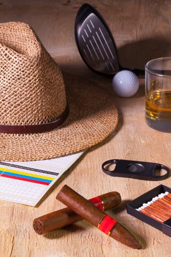 Siësta - sigaar, strohoed, Schotse whisky en golfbestuurder op een wo stock afbeeldingen