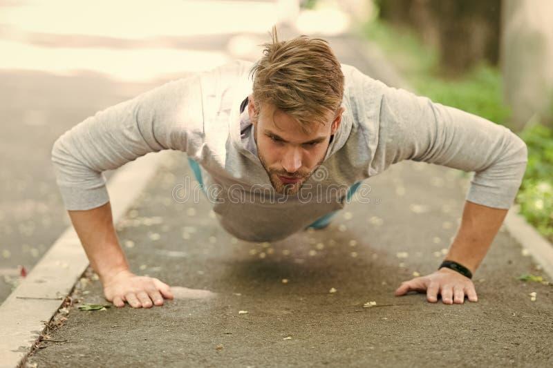 Siła i motywacja Mężczyzna w sportswear robić pcha podnosi plenerowego Faceta niepłonny trening w parku Sportowiec ulepsza jego zdjęcia stock