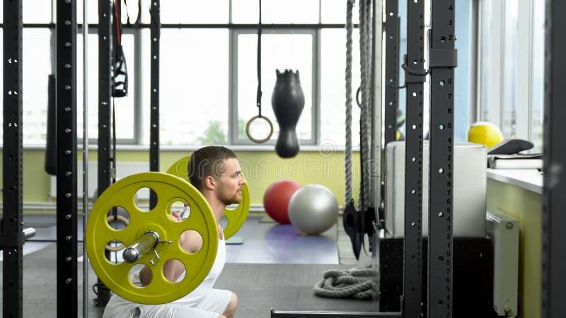 Siły szkolenie w gym facet robi kucnięciom z barbell bodybuilder robi ćwiczeniu z barbell Boczny widok fotografia royalty free