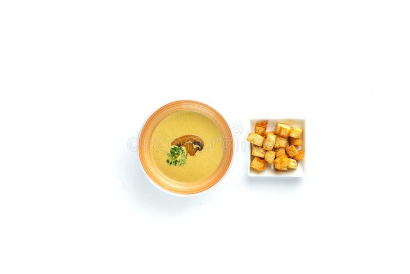 si espandono rapidamente la minestra ed i cracker crema in una tazza su un fondo bianco isolato fotografia stock