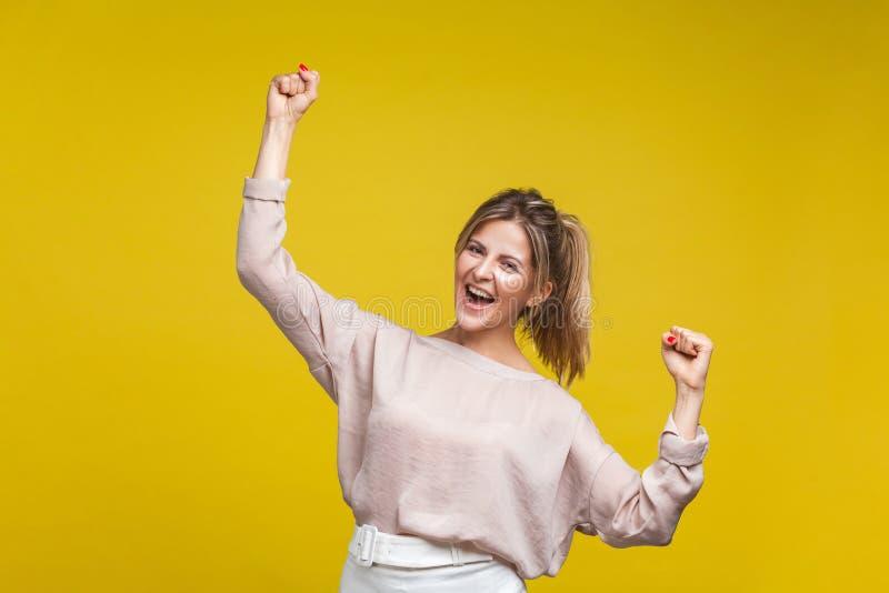 Si', l'ho fatto! Ritratto di una bellissima donna eccitata con capelli biondi in camicetta di beige, isolata su fondo giallo fotografia stock libera da diritti