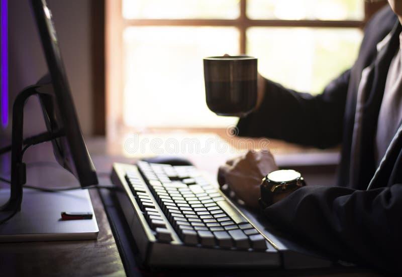Si?ntese y trabaje en el ordenador, sorba el caf? por la ma?ana imagen de archivo libre de regalías