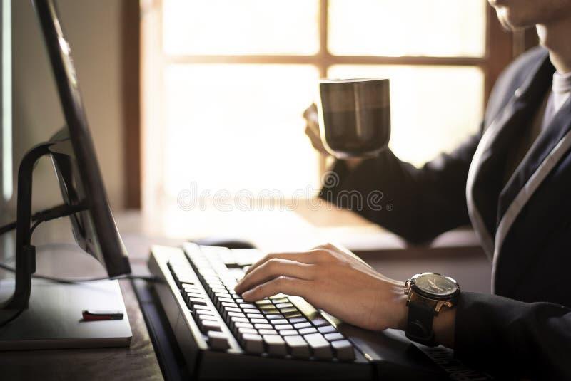 Si?ntese y trabaje en el ordenador, sorba el caf? por la ma?ana fotos de archivo libres de regalías