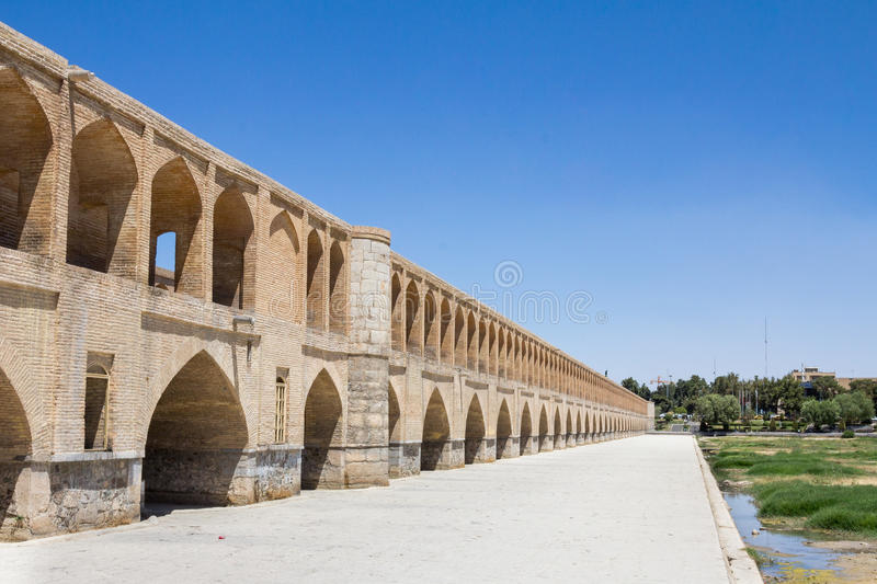 Si o Seh Pol bridge on a sunny day in summer in Isfahan, Iran. Picture of the iconic bridge of Si o Seh, in the center of Isfahan. The river Zayandeh is dry due royalty free stock photography