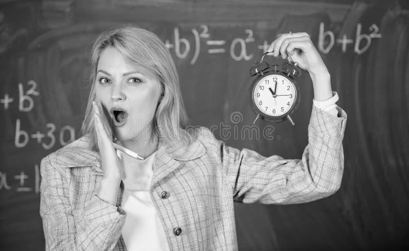 Si preoccupa per disciplina Che ore sono Sveglia della tenuta dell'insegnante della donna Conferenziere della scuola di usura con fotografia stock libera da diritti