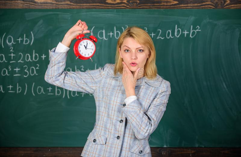 Si preoccupa per disciplina Sveglia della tenuta dell'insegnante della donna Conferenziere della scuola della ragazza Che ore son immagini stock libere da diritti