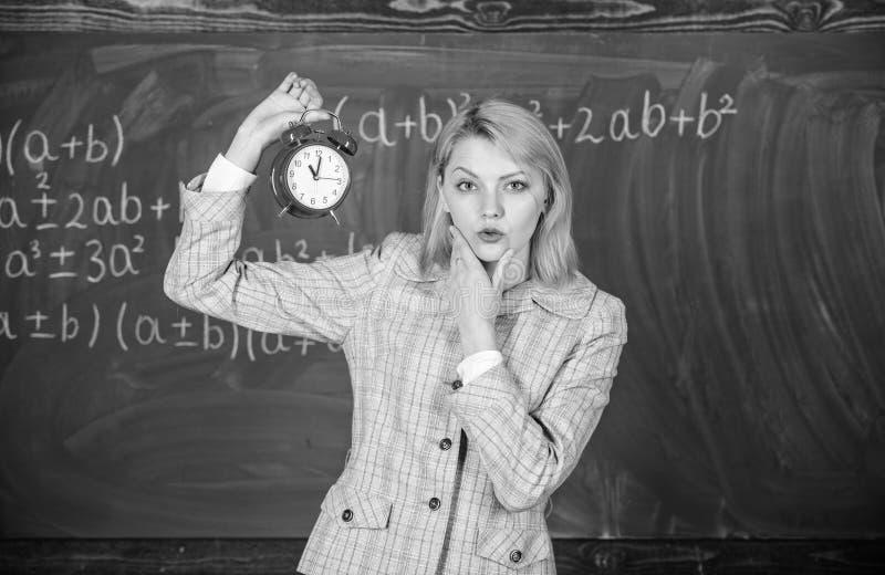 Si preoccupa per disciplina Sveglia della tenuta dell'insegnante della donna Conferenziere della scuola della ragazza Che ore son fotografie stock