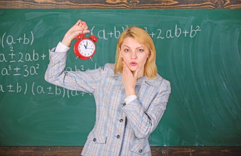 Si preoccupa per disciplina Sveglia della tenuta dell'insegnante della donna Conferenziere della scuola della ragazza Che ore son immagini stock