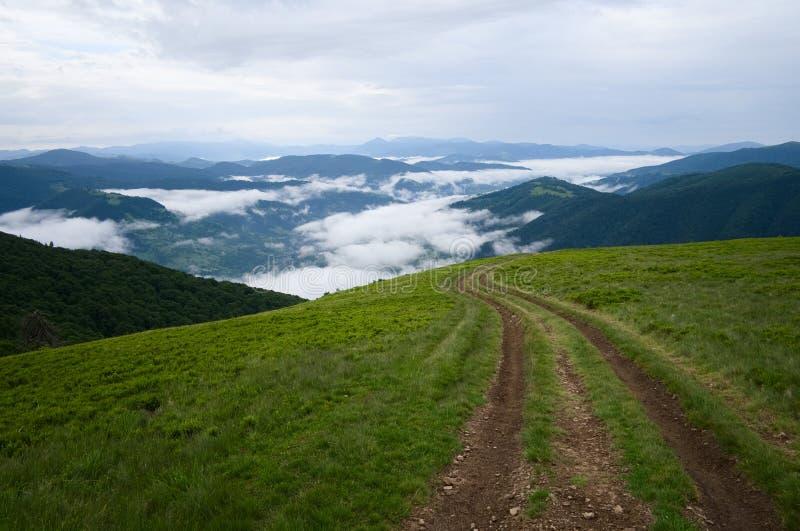 Si rannuvola le piste del paesaggio e della strada non asfaltata della montagna della valle sul prato verde fotografia stock