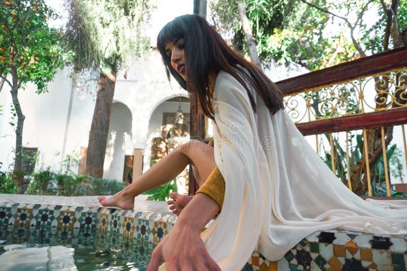 短的金黄礼服和白色披风斗篷的美丽的摩洛哥女孩在美丽如画的达尔Si富有的内部说Riyad 免版税库存图片